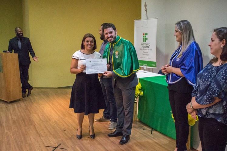 Formanda recebendo diploma do Diretor Geral Carlos Vinícius